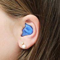 oreja de mujer con un tapón en el oído